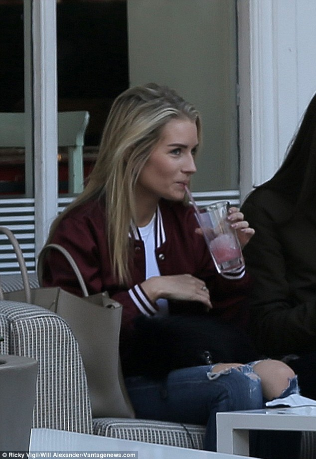 Drinking away:With her blonde tresses tumbling around her face and her chic varsity jacket, it was apparent the stunning star has youth on her side